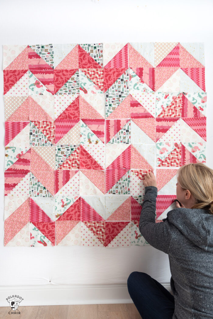 woman placing half square triangle quilt blocks on wall