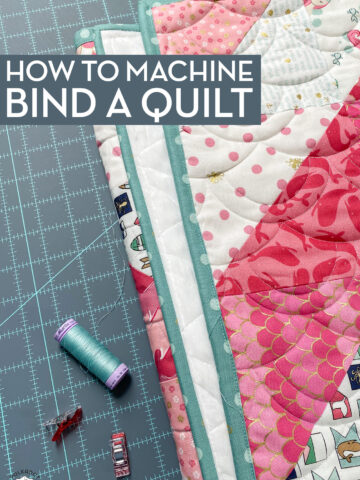quilt, thread and clips on blue cutting mat