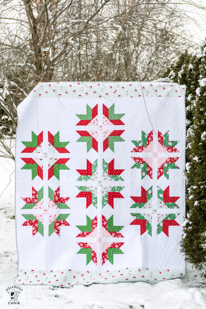 red, white and green quilt in snowy yard