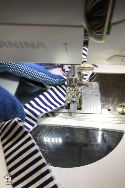 gloved hand holding a quilt under a sewing machine