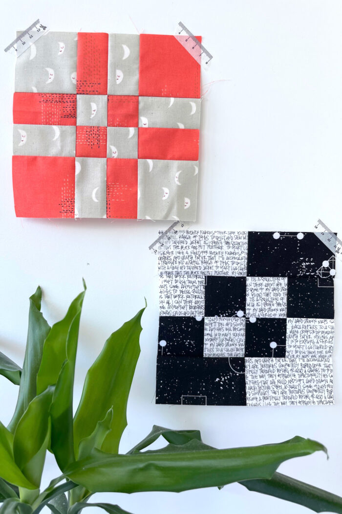 red, gray and black quilt blocks on white wall
