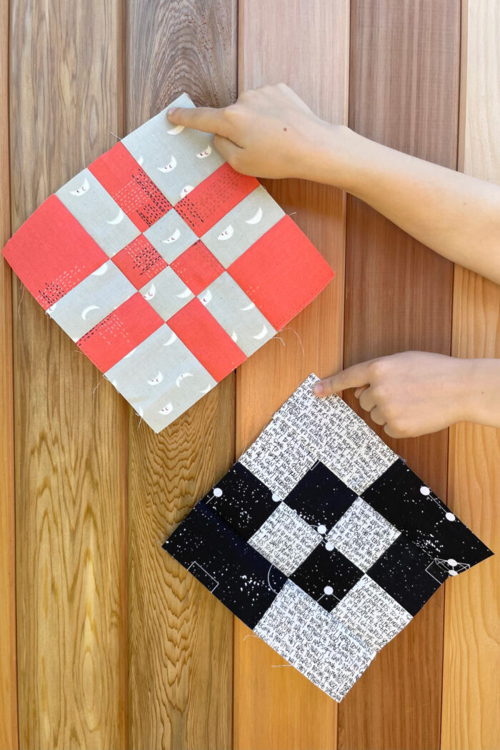 hands holding two quilt blocks in front of wood fence