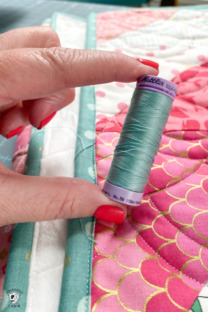 hand holding aqua thread