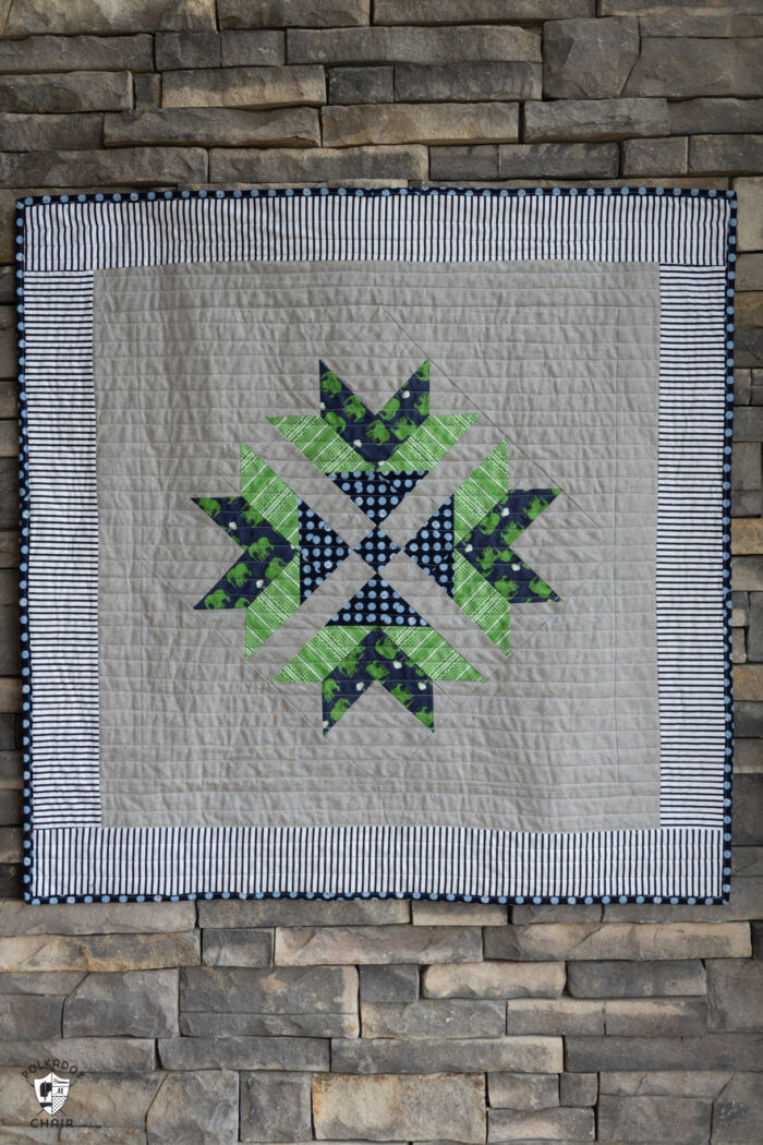 gray, navy and green quilt on stone wall