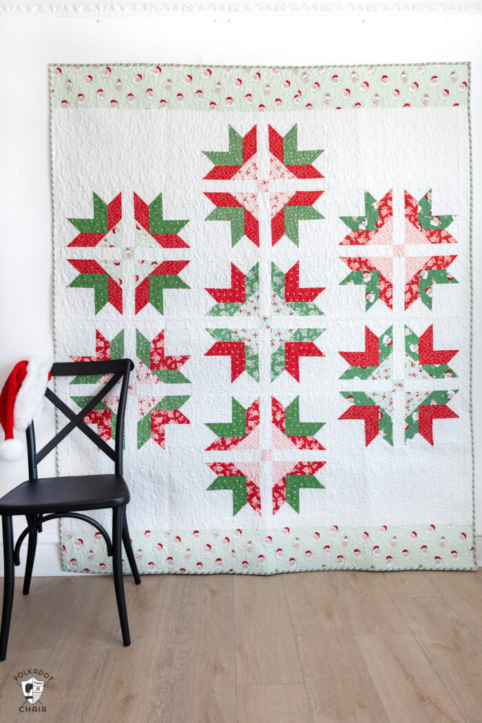 pink, red, green graphic quilt on white wall with black chair in foregroud.