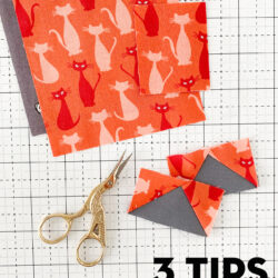 orange and gray quilt blocks with scissors on white cutting mat