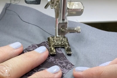 sewing machine foot sewing black and gray fabric