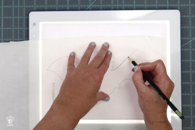 hands tracing a bat shape on light box