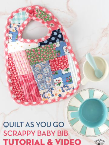 colorful scrappy baby bib on white marble tabletop with cups