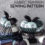 stack of fabric pumpkins on white table with gray background