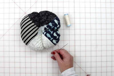hands constructing fabric pumpkin with tools on white cutting mat