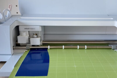 cricut machine with green cutting mat and blue vinyl