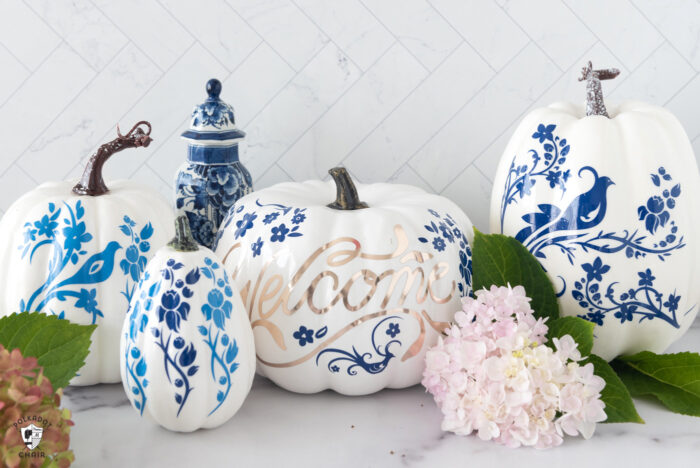 blue and white pumpkins on white table with flowers