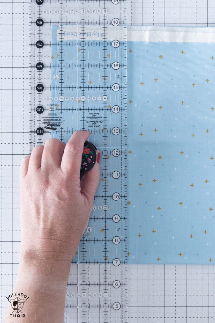 hand on quilt ruler on cutting mat with blue fabric