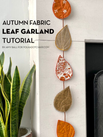 fabric leaves hanging from fireplace mantel decorated for autumn