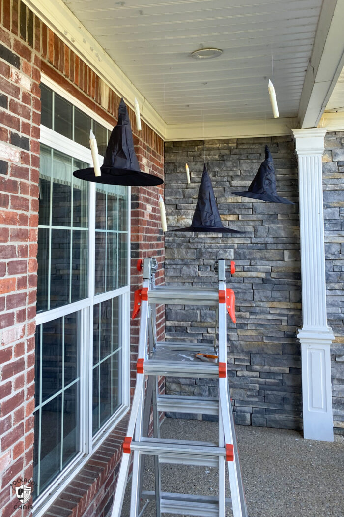 LED candles floating on front porch with black witch hats