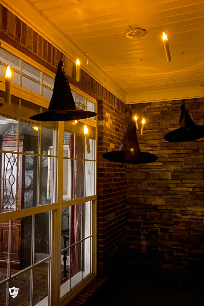 LED candles floating on front porch with black witch hats at night