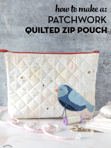 Ivory quilted zip pouch with blue bird on white countertop